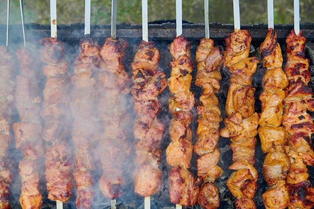 Pezzi di deliziosa carne alla brace su spiedino di cottura su carboni ardenti. carne di maiale arrosto cotta alla griglia. grigliata sulla natura. vista ravvicinata dall'alto.