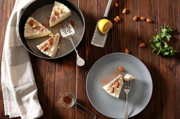Pezzi di deliziosa cheesecake con mandorle su tavola di legno