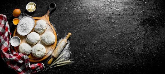 Pezzi di pasta con farina, uova e un tovagliolo sulla tavola rustica nera