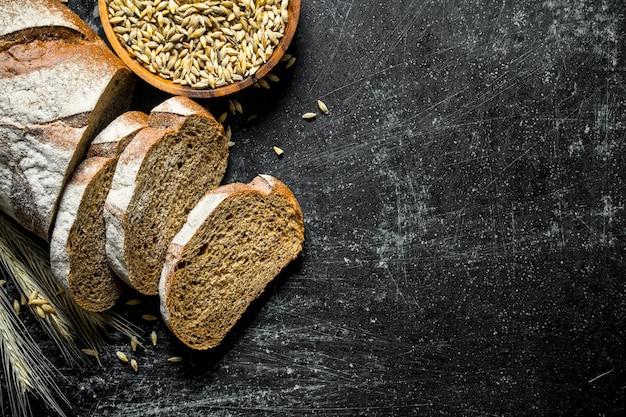 Pezzi di pane fresco con grano. sul nero rustico