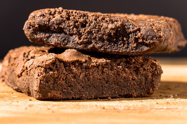 Pezzi di brownie fresco su fondo di legno. torta al cioccolato deliziosa. primo piano a macroistruzione. messa a fuoco selettiva.