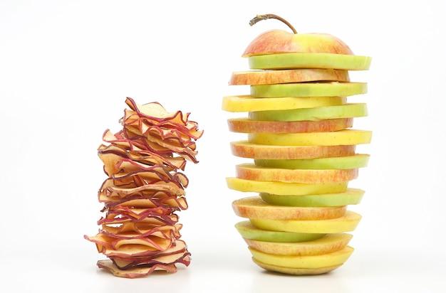 Pezzi di mele fresche e secche impilate a piramide su un bianco