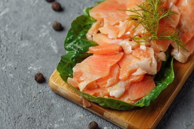 Pezzi di salmone fritto con aneto e spicchi di limone su una tavola di legno