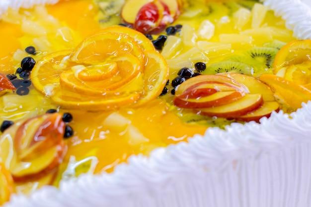 Pezzi di frutta in gelatina. dessert con crema bianca. succosa arancia e kiwi. la migliore ricetta di una torta sana.
