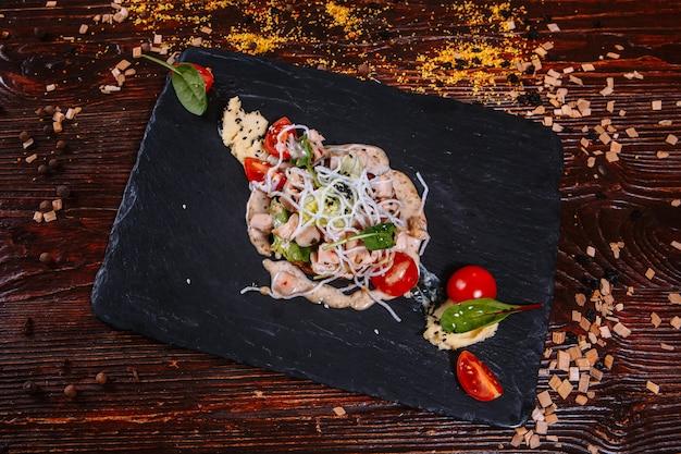 Pezzi di carne su un bordo nero con purea di piselli. sul tavolo