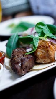 Pezzi di carne con cipolle su spiedini di kebab. servire con salsa su un piatto bianco.