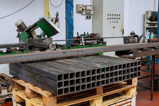 Pezzi di profilo metallico della stessa lunghezza. taglio di profili in acciaio su una sega a nastro in produzione.