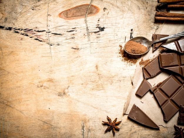 Pezzi di cioccolato al latte con cacao e cannella su fondo in legno