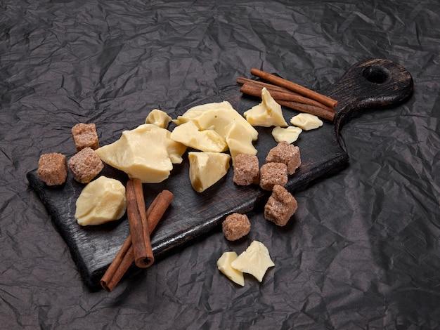Pezzi di burro di cacao naturale con cannella e zucchero di canna su sfondo nero. con copia spazio