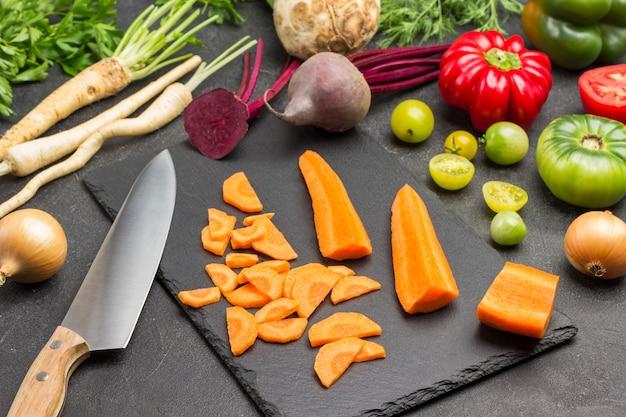Pezzi di carote sbucciate, coltello da cucina sul tagliere. prezzemolo, barbabietole e pomodori sul tavolo. sfondo nero. vista dall'alto