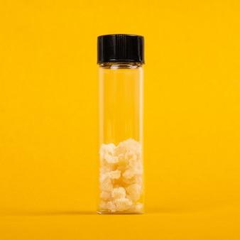 Un pezzo di puro hashish dab crystal cannabis su sfondo giallo.