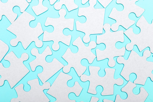 Pezzi di un puzzle collegati su uno sfondo blu con molti altri pezzi del puzzle. concetto di lavoro di squadra di affari