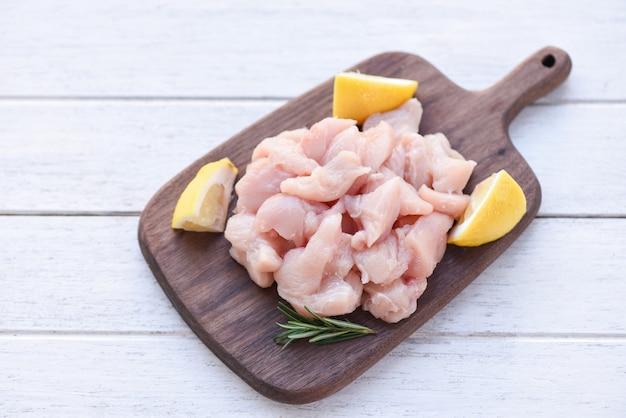 Pezzi di carne di pollo cruda con rosmarino e limone / filetto di pollo crudo fresco tagliato sul fondo del tagliere di legno