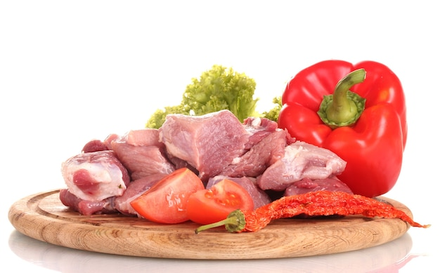 Pezzi di carne cruda e verdure su tavola di legno su bianco