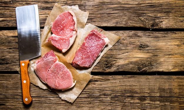 Pezzi di carne cruda con un coltello da macellaio. sullo sfondo di legno. spazio libero per il testo. vista dall'alto