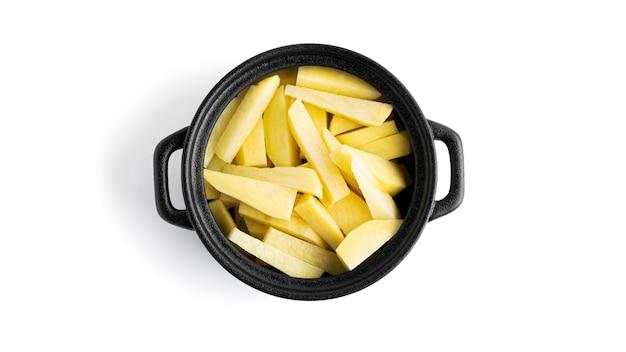 Pezzi di patate crude in una pentola nera isolata su una superficie bianca