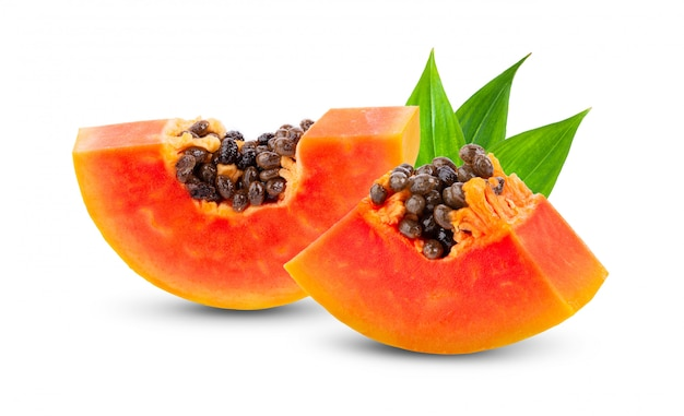 Pezzi di frutta matura della papaia con i semi sulla parete bianca