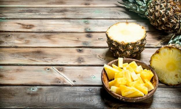 Pezzi di ananas maturo in una ciotola. sulla tavola di legno