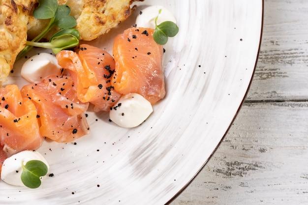 Pezzi di salmone salato su un piatto bianco.