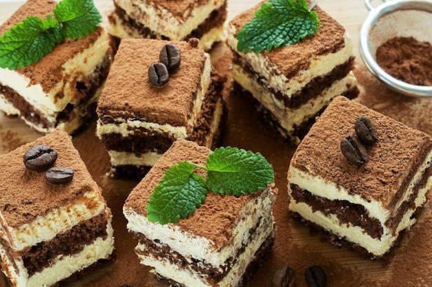 Pezzi di torta tiramisù con delicata crema, chicchi di caffè e foglie di menta.