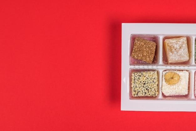 Pezzi di delizia turca in un contenitore di plastica su sfondo rosso. dolci orientali. disposizione piatta.