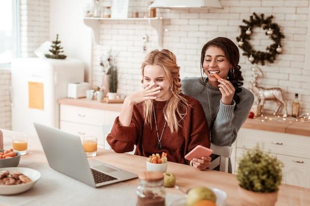 Pezzi di verdure. ragazze attraenti positive che mangiano spuntini sani e osservano video sulla zona cucina