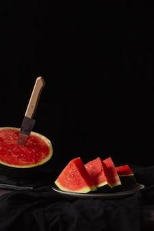 Pezzi di anguria su sfondo nero e un coltello. stile rustico.