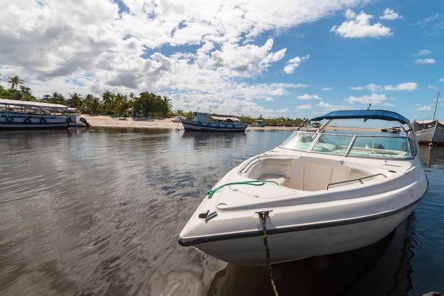 Molo sull'isola tropicale con barche e motoscafi.