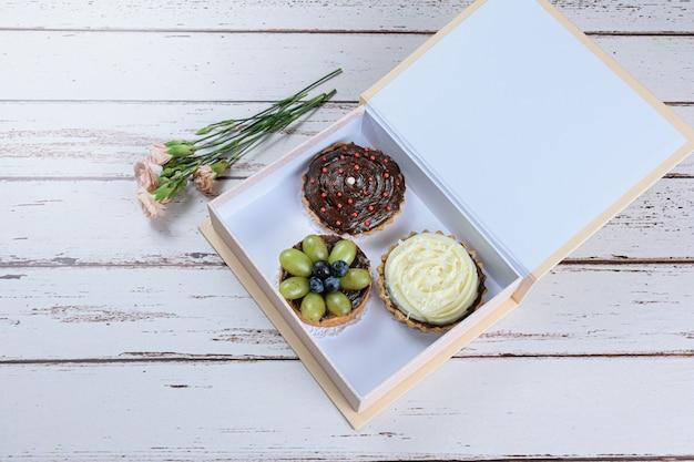 Torte con pasta burrosa ripiene di ganache al cioccolato con varie farciture, all'interno di una confezione regalo e accanto alle rose.