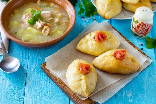 Torte con salmone e zuppa sul tavolo di legno della cucina cucina tradizionale russa