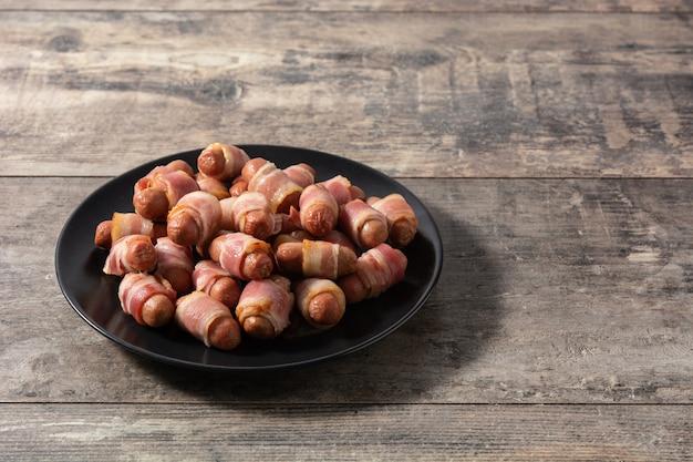 Maiale in coperte. salsicce avvolte in pancetta affumicata sul tavolo di legno
