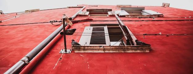 I piccioni riposano sulla facciata della vecchia casa rossa nel centro storico. rovigno, croazia