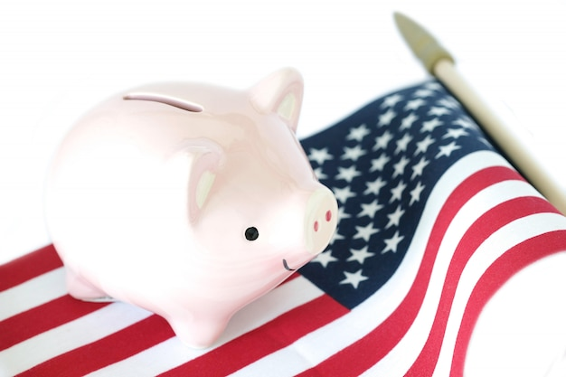 Porcellino salvadanaio sulla bandiera americana su fondo bianco. concetto di condizione economica.