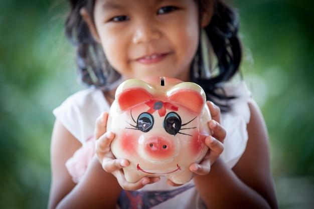 Piggy bank sulla mano bambina asiatica