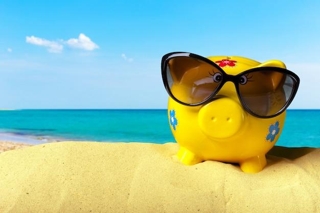 Salvadanaio su una spiaggia. concetto di risparmio di vacanza