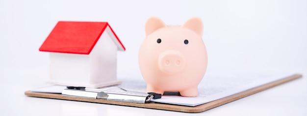 Salvadanaio, bellissimo modello di casa in legno su un contratto firmato su sfondo bianco, concetto di risparmio di denaro per acquistare un'assicurazione sulla casa, primo piano, copia spazio.