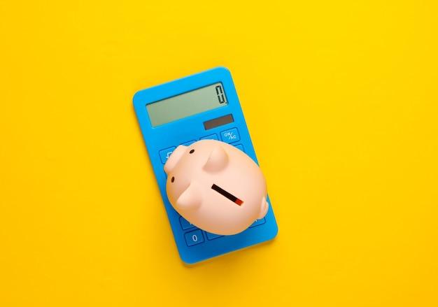 Salvadanaio e calcolatrice blu su giallo
