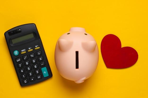Salvadanaio, calcolatrice e cuore su colore giallo