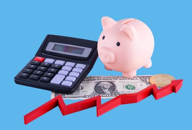 Salvadanaio, calcolatrice, denaro, bitcoin e freccia rossa su sfondo blu