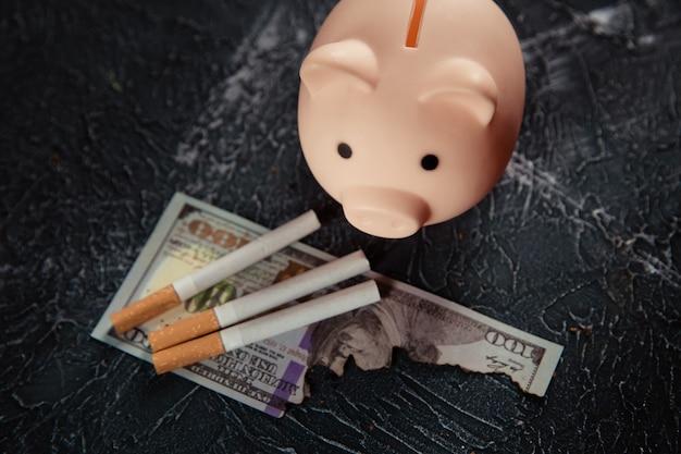 Salvadanaio e sigarette sul tavolo scuro. abitudine costosa