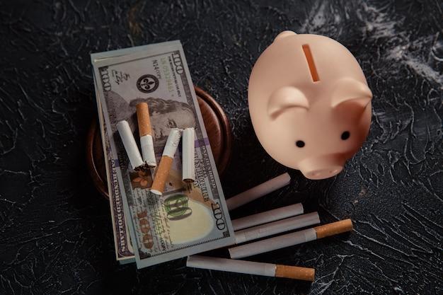 Salvadanaio e sigarette sulla superficie grigia. abitudine costosa e pericolosa