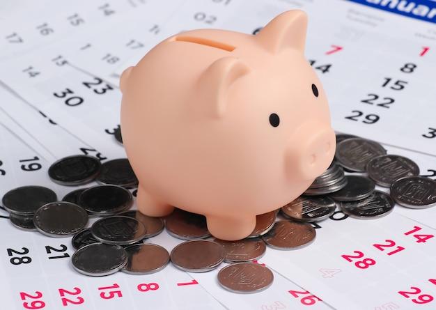 Salvadanaio e monete sul calendario mensile, risparmio di denaro, ricchezza e denaro per gli investimenti