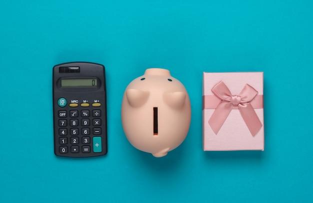 Salvadanaio e confezione regalo, calcolatrice sull'azzurro.