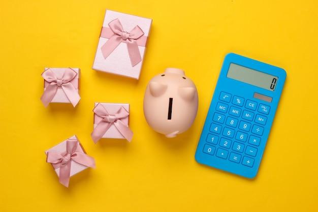 Salvadanaio e scatole regalo, calcolatrice su giallo