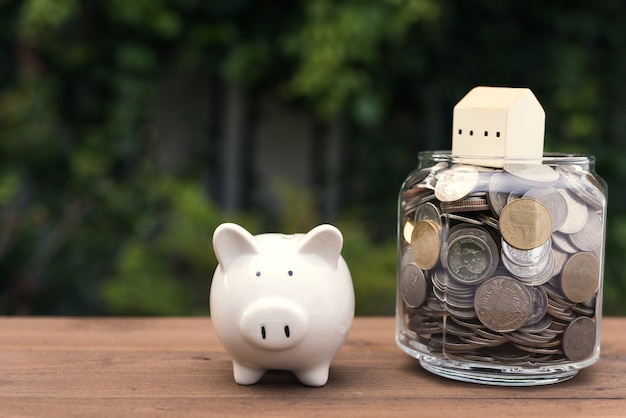 Salvadanaio e modello di casa su denaro monete vaso di vetro su tavola di legno, risparmio e concetto di investimento