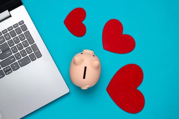 Salvadanaio, laptop, cuori sull'azzurro