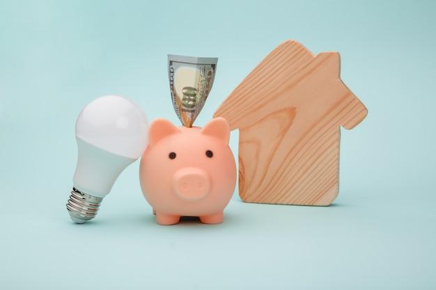 Salvadanaio e lampadina a led, figura di casa sulla superficie blu. concetto di risparmio energetico