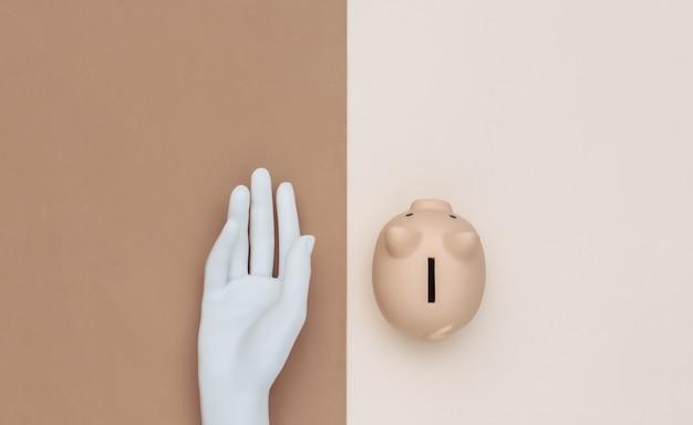 Salvadanaio e manichino a mano su fondo beige marrone. minimalismo piatto. vista dall'alto.