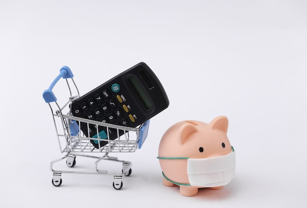 Salvadanaio in una maschera medica e carrello della spesa con calcolatrice su sfondo bianco. shopping durante covid-19, crisi economica, economia
