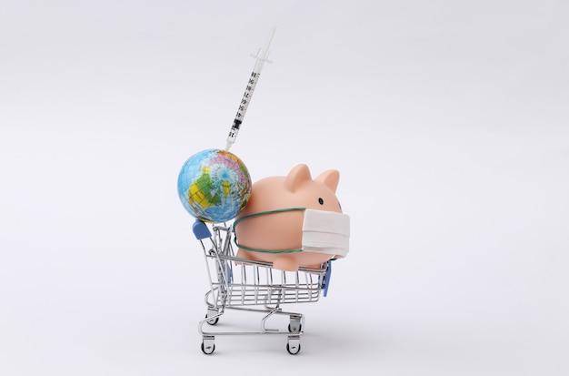 Salvadanaio in maschera medica e carrello della spesa con globo, siringa su sfondo bianco. vaccinazione. pandemia di covid-19